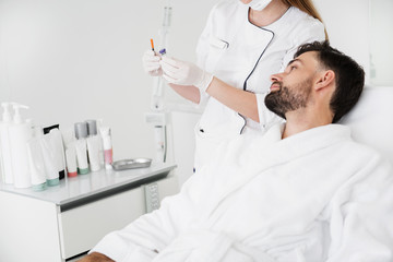 Cosmetologist holding injection and calm man looking at it