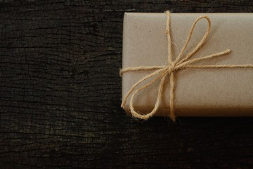 Simple eco friendly gift boxes package wrap with brown paper in old wooden table background, green present concept