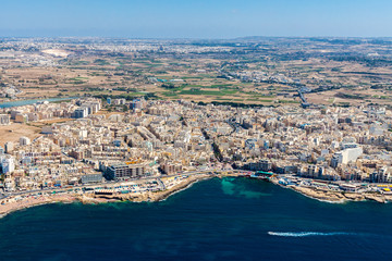 Aerial view of Bugibba town, St. Paul's Bay in the Northern Region, Malta. Popular tourist resort destination with promenade, hotels, restaurants, pubs, clubs, and a casino.