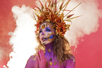 Bright Halloween image, Mexican style with sugar skulls on face. Young beautiful woman bright pink skin