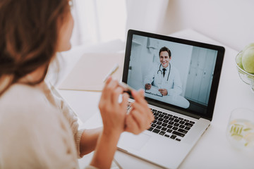 Cheerful doctor making video-call to his patient at home