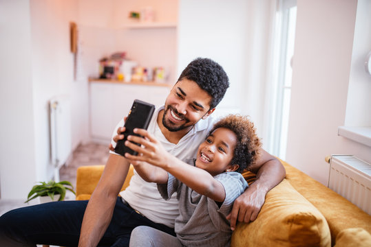 Happy african american father and daughter making a selfie at home.
