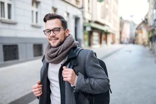 Portrait of a trendy young man with backpack walking in the city street. Looking at camera.