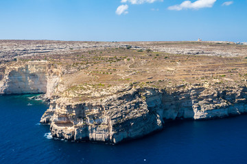Cliffs and blue lagoons of Gozo island seen from above. Aerial view of Gozo, Malta. The Rotunda of Xewkija (Casal Xeuchia) is the largest in Gozo island and its dome dominates the island everywhere.