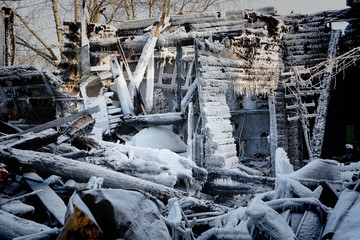 The ruins of a wooden house after a fire in winter