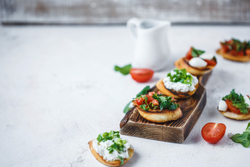several types of italian bruschetta with tomatoes, mozzarella and herbs on a wooden board on a light background
