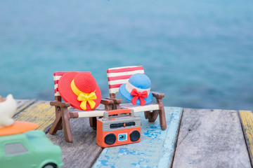 Miniature hats on beach chair with sea background.Vacation concept.