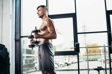 side view of handsome shirtless sportsman training with dumbbells in gym