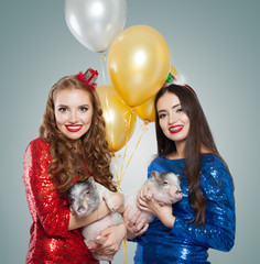 Perfect smiling women in party dress and little pigs, holiday concept