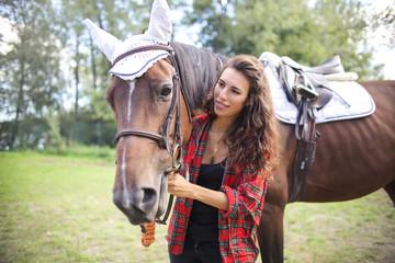 Cute girl stroking her horse