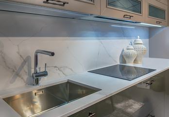 Fragment of the interior of modern cuisine. Marble table top with tap, metal sink and induction hob