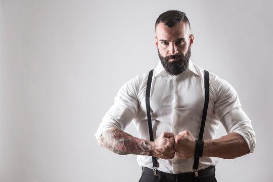 Uomo muscoloso tatuato  con camicia bianca e bretelle chiude i pugni deciso su sfondo bianco