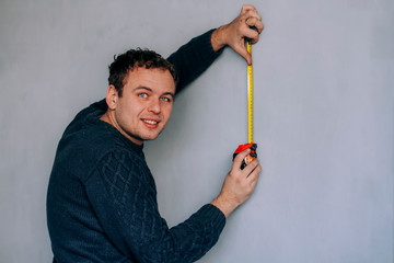 A man measures the length of the wall with a tape measure
