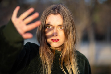 Lovely young female with bright makeup trying to cover face with hand from sunlight while standing on blurred background of park