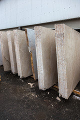 Side view of the edge of the granite slab in bulk. A stack of granite slabs - marble factory. Background of marble slabs. Natural stone. Background of granite slabs. Granite slabs ready for sale