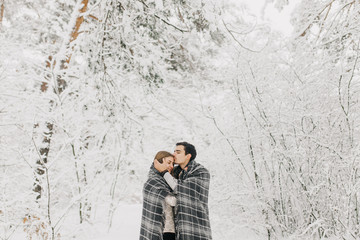 couple in love walking in the snowy forest, hugging, kissing and enjoying
