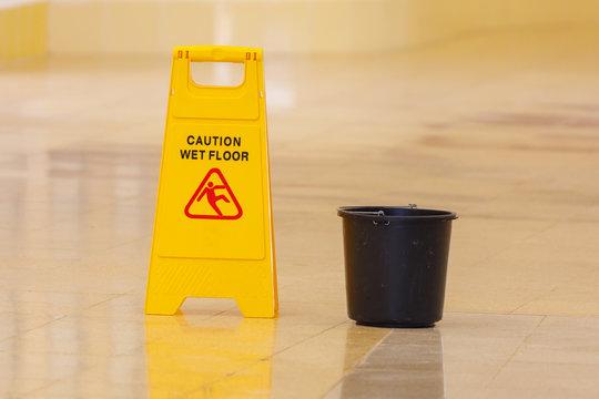 Wet floor caution sign and black plastic bucket