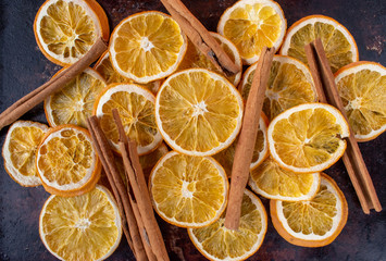 pile of dried orange slices and cinnamon sticks on dark background flat lay