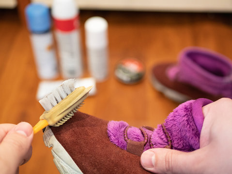 man cleans suede shoe with special brush. care product set for nubuk leather out of focus on background. selective focus on foreground