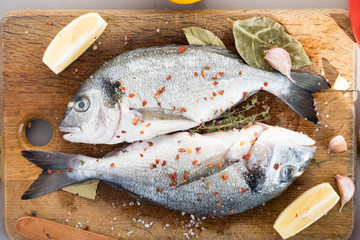 Two sea fish with flavored seasonings lie on a wooden board with two fish sprinkled with flavored seasonings. Cooking process
