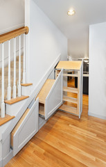 Under-stair pullout cabinets installed in openings with decorative fronts attached (but no handles)