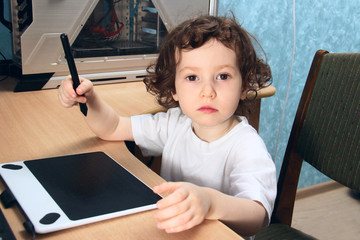Little 2 3 year old baby girl in white clothers draws at the home computer in graphics drawing tablet. The child is holding a pen