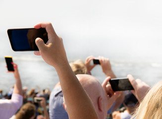 A group of people are taking a picture with mobile phones