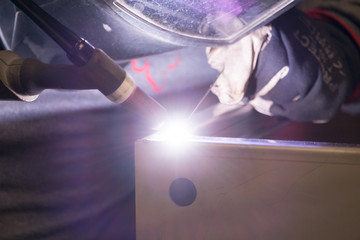 Professional welder in his industrial workshop welding metal
