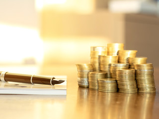 Invest your money to get in come,growing business and future concept, coins stack and pen and book on wooden table