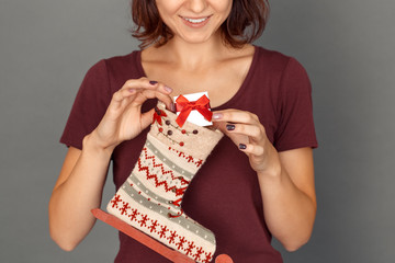 Freestyle. Young woman isolated on grey putting gift into decorated sock smiling cheerful close-up