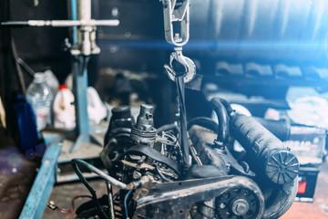 Engine instalation on crane hook on car repair service