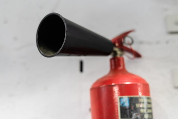 Red fire extinguisher on white wall background, ready to use