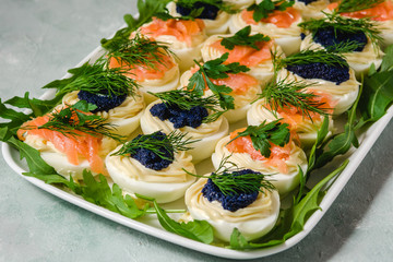 Stuffed eggs with salmon and caviar decorated by parsley and dill. Party food