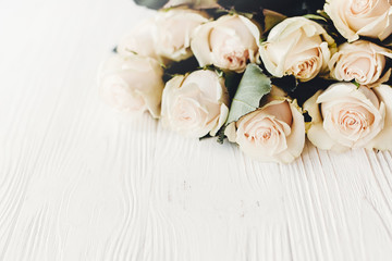 Floral greeting card mockup. White roses on wooden background, space for text. Wedding invitation or happy mother day or valentines concept. Bouquet of white flowers