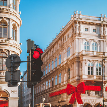 Selective focus of giant decorative red Christmas bow on building with red traffic light in the foreground