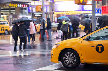 Yellow cab speeds through Times Square, the busy tourist intersection of neon art and commerce.