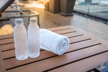 Two drinking bottle of water with white towel on wooden table