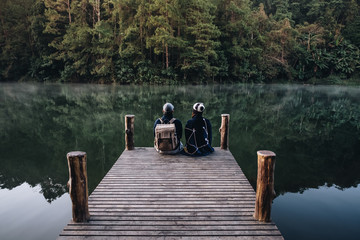 Couple of Asian Traveler on the Bamboo bridge beside the lake in the mist at morning sunrise at Pang Ung , Mae Hong Son province, Thailand