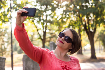 Beautiful Girl in Pink Blouse Smiling and Taking Selfie in a Park
