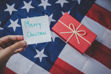 Christmas and New Year's Day, Close up holding hand note pad with message and Red gift box and ribbon with flag of the united states in the background.