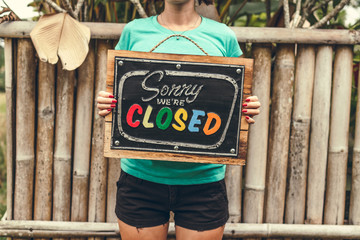 Closed sign wooden board in woman hands. Bali island background.