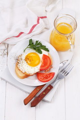fried eggs on a piece of white bread and orange juice