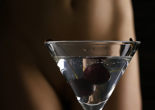 cocktail with cherry and blured female buttocks in white panties in a dark background. dating and party concept.