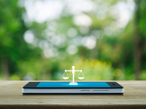 Law flat icon on modern smart mobile phone screen on wooden table over blur green tree in park, Business legal service online concept