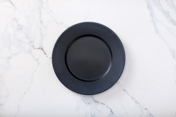 Black plate on marble countertop.