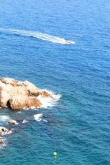 Sea view of a sailing boat and coastal cliffs in Spain.