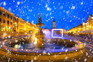 Fountain on the main square of Bialystok at night with falling snow, Poland.