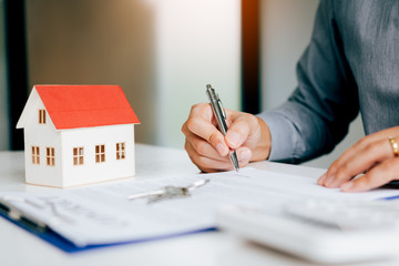 Close up hand man signing paper contract agreement for buying house.