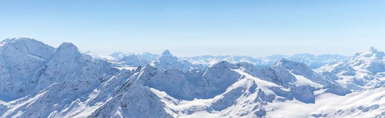 White snowy winter Caucasus mountains at sunny day. Panorama view from ski slope Elbrus, Russia Wall mural