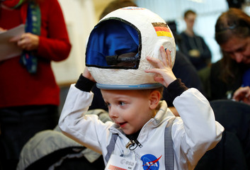 Four-year-old Joshua puts up his self-made helmet before a news conference with German astronaut Alexander Gerst near Cologne